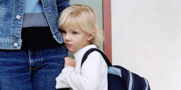 Girl (4-6) with backpack clinging on to mother