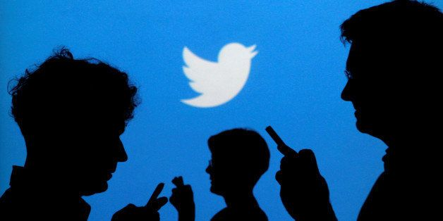 FILE PHOTO --  People holding mobile phones are silhouetted against a backdrop projected with the Twitter logo in this illust