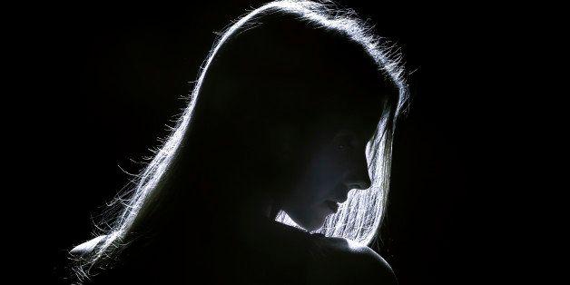 sad woman profile silhouette in dark