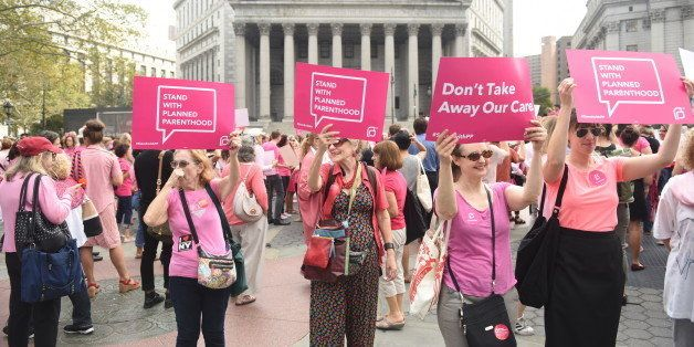MANHATTAN, NEW YORK CITY, NEW YORK, UNITED STATES - 2015/09/29: Planned Parenthood activists in pink hold signs in front the