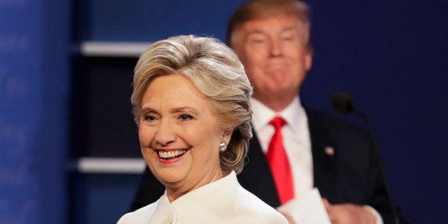 Democratic presidential nominee Hillary Clinton walks off stage as Republican presidential nominee Donald Trump puts his note