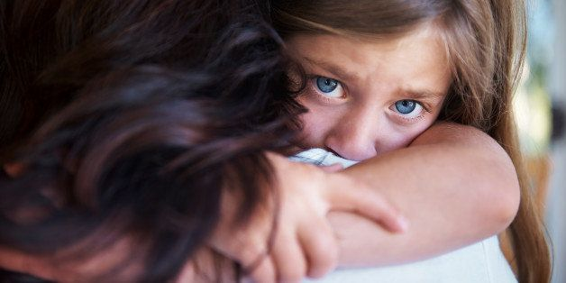 Closeup shot of a upset little girl hugging her mom around the neck