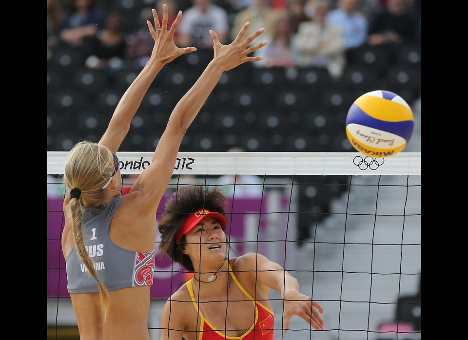 Zhang Xi, right, from China spikes a ball past Anastasia Vasina, left, from russia during their Beach Volleyball match at the