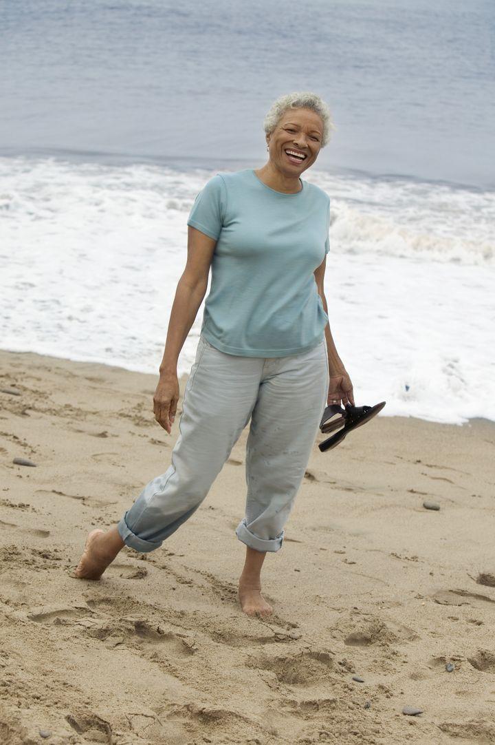 Smiling Woman Walking Barefoot on Beach