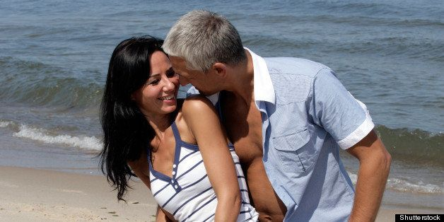 Happy middle aged couple kneeing on the beach, enjoying their summer holiday together.