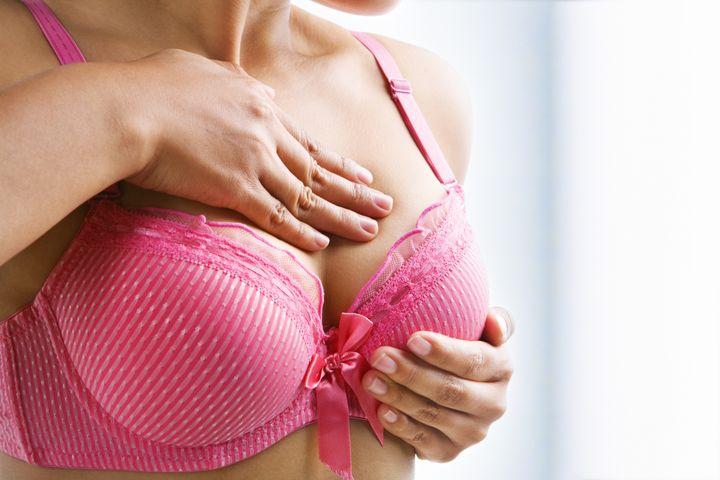 Woman doing self breast examination using pink bra