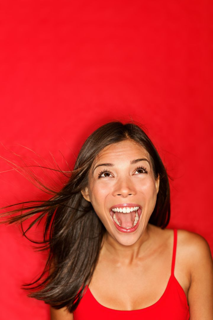 surprised screaming woman looking up at copy space on red background. Beautiful young shocked mixed race Caucasian / Asian fe