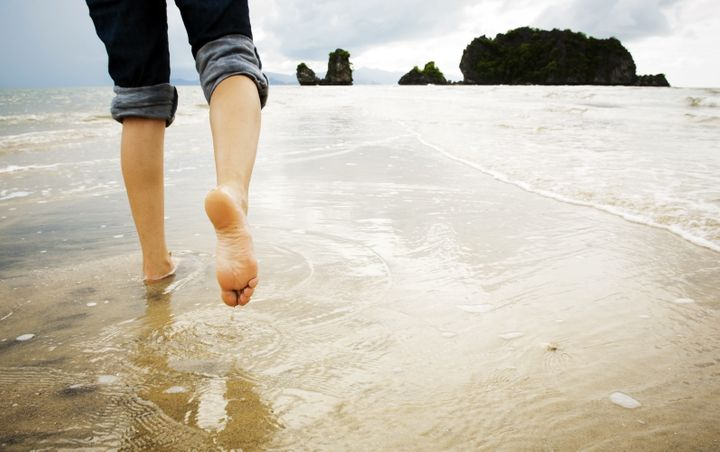 A young woman walks alone on a beach, just her feet and legs showing