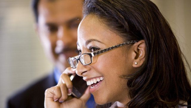 Young mixed-race Hispanic African-American woman talking on mobile phone
