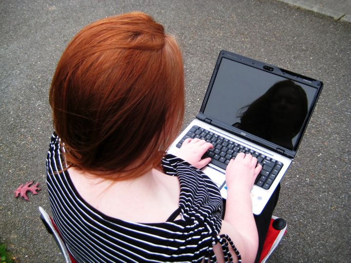 Woman and her Reflection on Laptop as she sends her email across the internet with wireless technology.