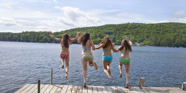 Four teenage girls jumping off a dock at a lake, holding hands.  Image depicts the joy of summer vacation and friendship.