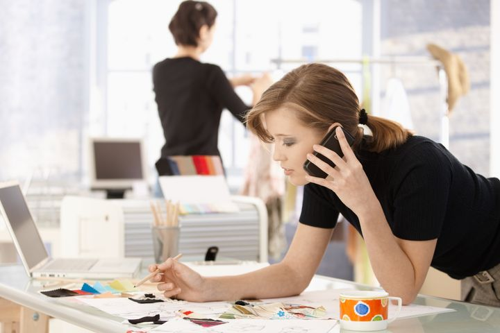 Young attractive female fashion designer leaning on office desk, talking on mobile phone.?