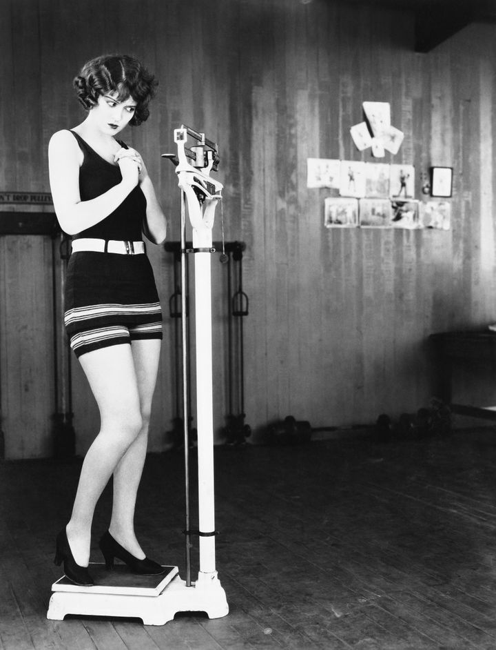 Profile of a young woman measuring her weight on a weighing scale