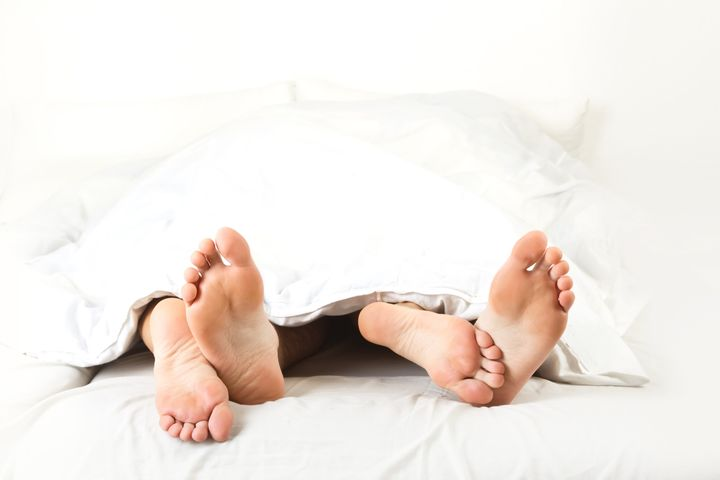 Foot of two people in the bedroom, on white background