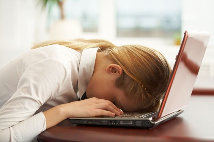 Image of very tired businesswoman or student with her face on keyboard of laptop