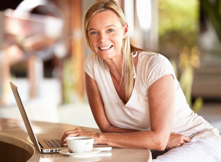 Beautiful mature woman smiling while using laptop at the hotel lobby