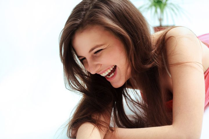 Happy woman laughing against white background