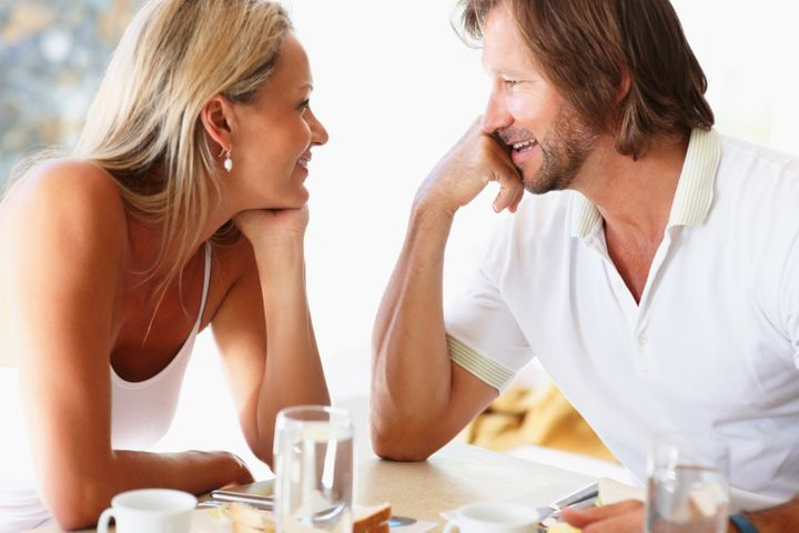 Portrait of a romantic mature couple looking at each other at dining table