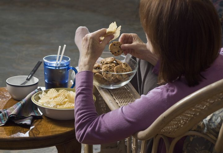 woman seated eating junk food