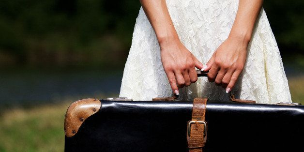 hands of a young woman with a suitcase