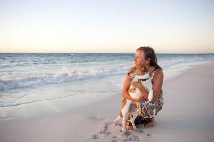 Happy looking mature woman is enjoying a sunset at the beach with her pet dog, with ocean and twilight sky as background and