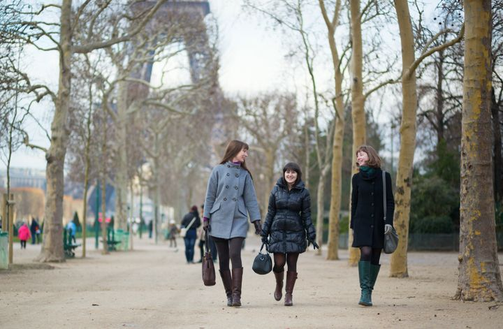 Three cheerful friends walking together in Paris