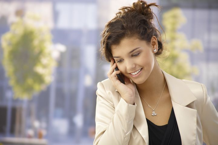 Pretty young woman talking on mobilephone outdoors, smiling happy.
