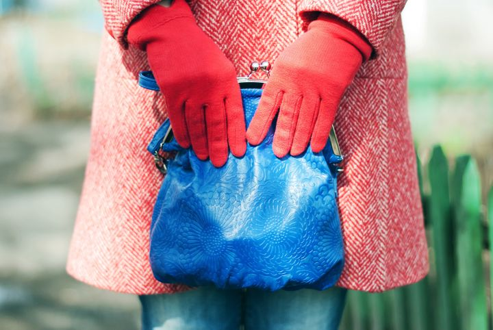 A fashion close up of a woman in a red spring-autumn wool topcoat, blue jeans and red gloves. Woman is holding a blue leather