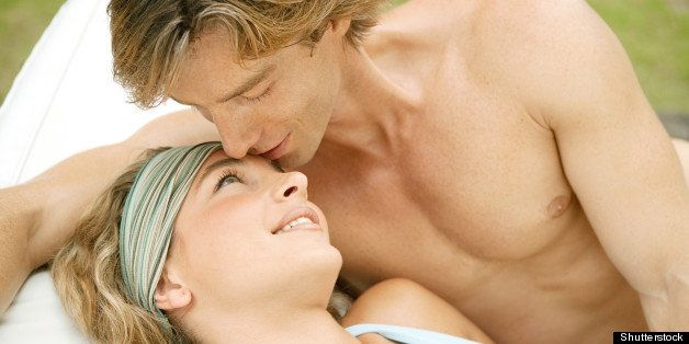 Portrait of a young couple relaxing on a sun bed and kissing, outdoors.
