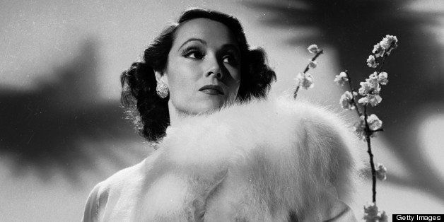 circa 1931:  Mexican film star, Dolores Del Rio (1905 - 1983) stands on a polar bear skin rug in a fur-trimmed coat.  (Photo