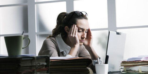 Exhausted businesswoman having a headache.