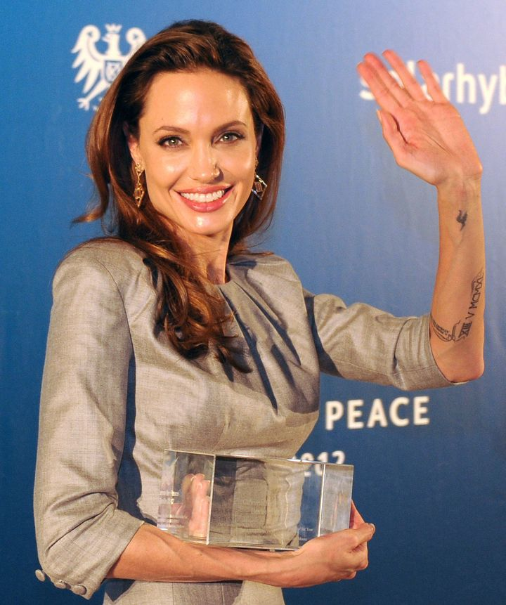 US actress Angelina Jolie poses with the 'Honorary Award for opposing War and Genocide' she received for her film 'In the Lan