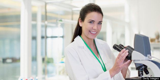Portrait of confident scientist using microscope in laboratory