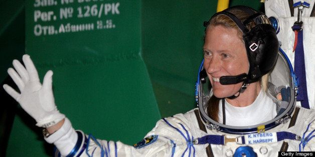 US astronaut Karen Nyberg waves as she board the Soyuz TMA-09M spacecraft at the Russian-leased Baikonur cosmodrome  on May 2