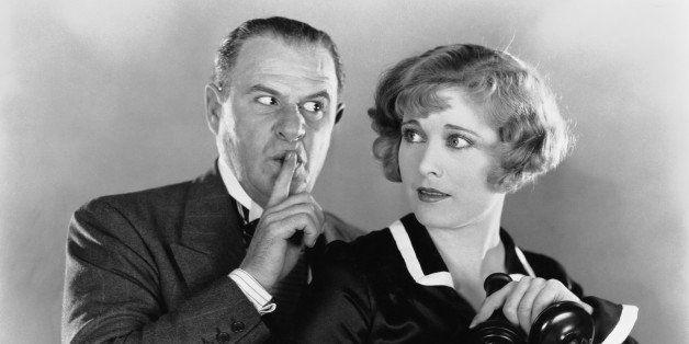 man shushing woman on telephone