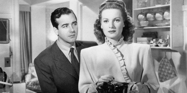 John Payne stands in back of Maureen O'Hara as she holds a coffee pot in a scene from the film 'Miracle On 34th Street', 1947