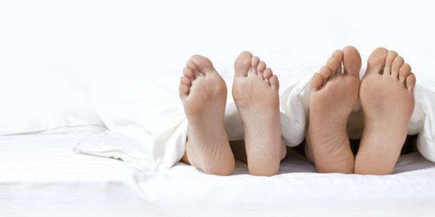 couple's feet on the bed