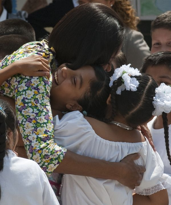 Here Michelle bends down to embrace not one but three children during a visit to Mexico City in 2010. No small feat for a wom