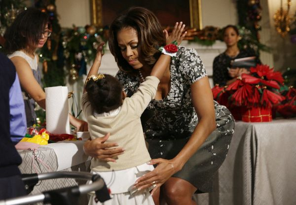 Take a cue from the famously fit First Lady: Kid hugs are a great way to work squats into your exercise routine.