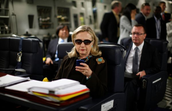 U.S. Secretary of State Hillary Rodham Clinton works from a desk inside a C-17 military plane upon her departure from Malta,