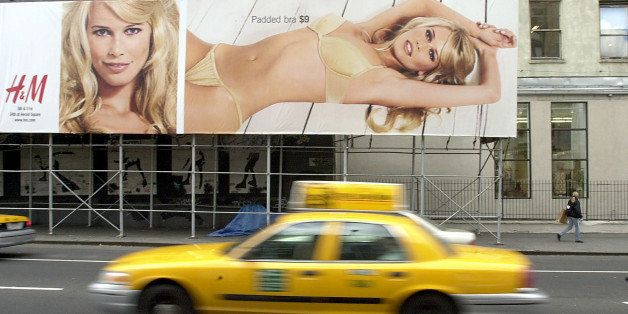 383191 03: A taxicab drives by a billboard featuring model Claudia Schiffer advertising the winter underware collection of cl