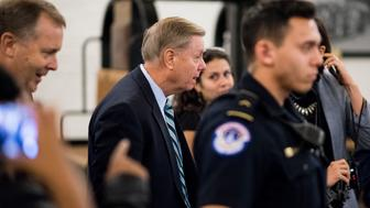 UNITED STATES - SEPTEMBER 29: Capitol Police escort Sen. Lindsey Graham, R-S.C., through a handful of protesters and the media to the Senate subway in the Russell Senate Office Building on Tuesday, Oct. 2, 2018. (Photo By Bill Clark/CQ Roll Call)