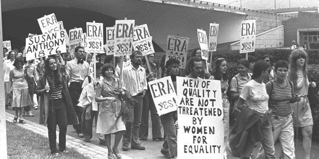 A group of men and women march together holding signs while participating in an ERA protest in Pittsburgh, PA, 1976. (Photo b
