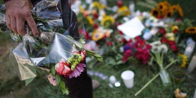 ISLA VISTA , CA - MAY 25: A man places flowers on the lawn of the Alpha Phi sorority house May 25, 2014 in Isla Vista, Califo