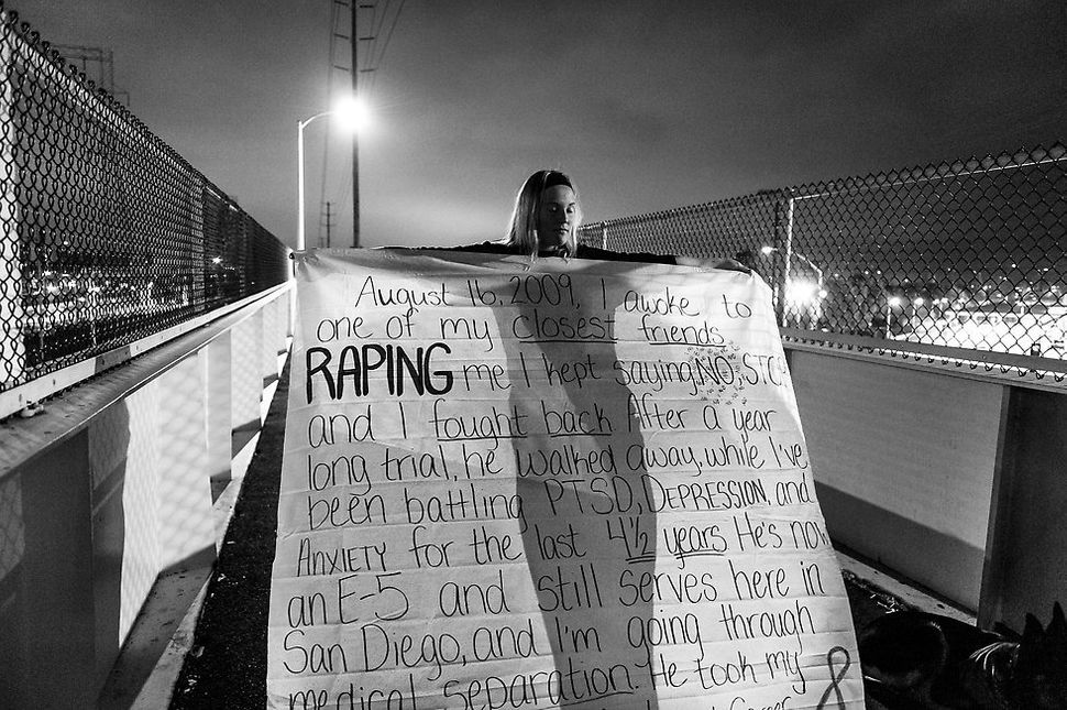April 21, 2014 -- San Diego, California: Melissa Bania holds her banner before hanging it on the foot bridge across from the