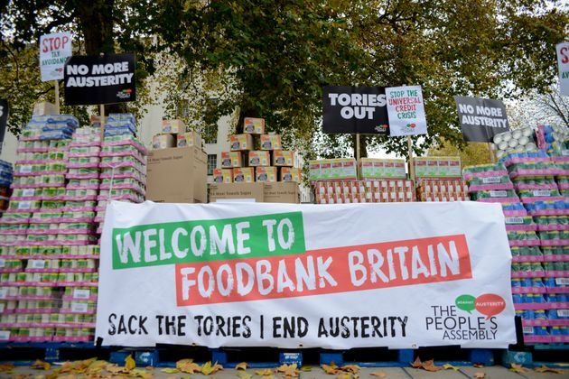 Campaigners protest against government austerity programmes next to crates of tinned food destined for food banks outside Downing Street in 2017