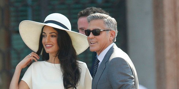 George Clooney, flanked by his wife Amal Alamuddin, arrives at the city hall for their civil marriage ceremony in Venice, Ita