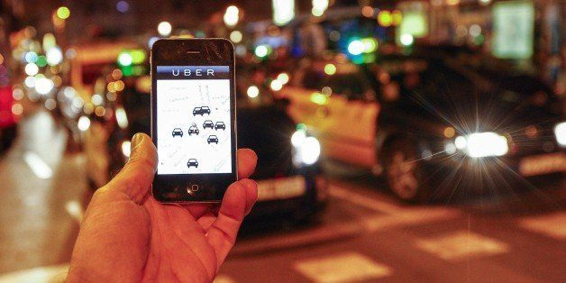 The Uber app is seen on a smartphone past cabs passing on Paseo de Gracia in Barcelona, on December 9, 2014. A judge on Decem