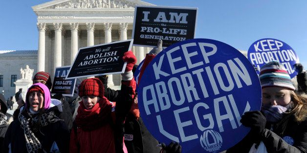 Pro-abortion and anti-abortion protestors rally outside the Supreme Court in Washington, Wednesday, Jan. 22, 2014. Thousands