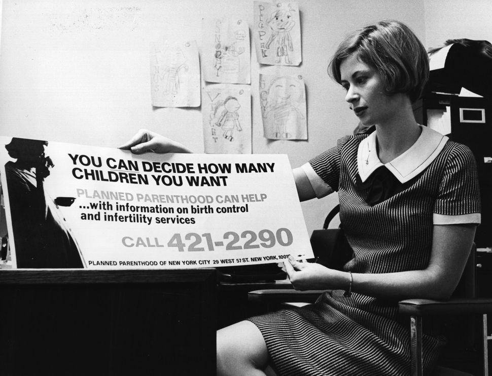 <strong>1967</strong>: Birth Control information on New York buses is held up for scrutiny by Marcia Goldstein, the publicity